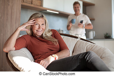 attractive mature woman with smartphone sitting in a comfortable chair .