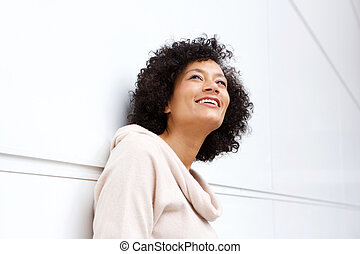 Close up attractive middle age african american woman smiling in contemplation