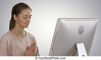 Attractive woman in a chair at the table with computer meditating on gradient background.