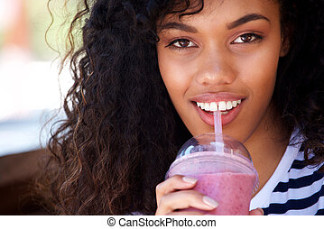 Close up attractive young african american woman drinking smoothie