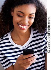 Close up attractive young african american woman looking at cell phone