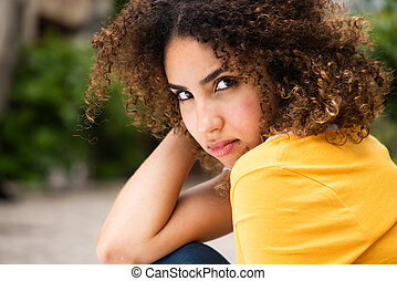 Close up attractive young african american woman with curly hair sitting outside