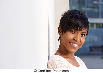 Close up attractive young african woman leaning to wall outside