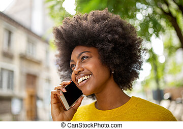 Close up attractive young african woman smiling and talking with cellphone outside