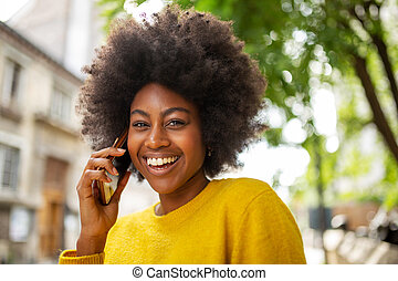 Close up attractive young african woman smiling and talking with mobile phone outside