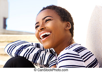Close up attractive young black woman laughing outside