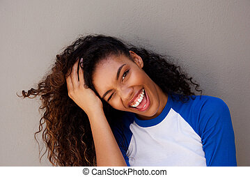 Close up attractive young black woman smiling with hand in hair against gray wall