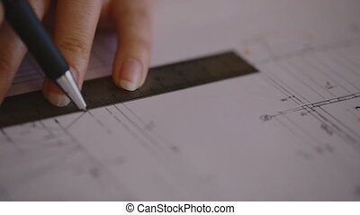 Close-up Attractive young female architect working at desk with plans on blueprint using the compass and enter the data into an electronic tablet