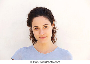 Close up attractive young woman against white wall