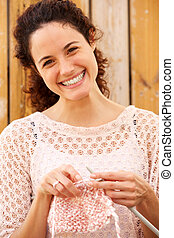 Close up attractive young woman smiling and knitting sweater