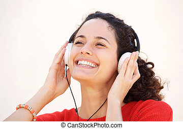 Close up attractive young woman smiling and listening too music with headphones