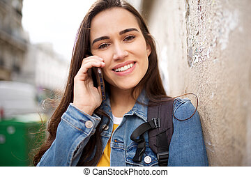 Close up attractive young woman smiling and talking with mobile phone