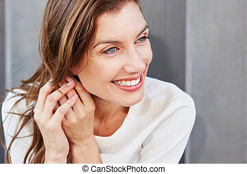 Close up attractive young woman smiling with hand in hair