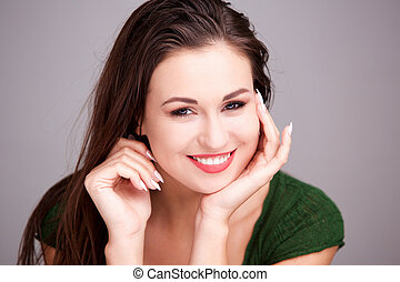 Close up attractive young woman smiling with hand on face