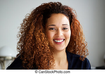 Close up attractive young woman with curly hair smiling
