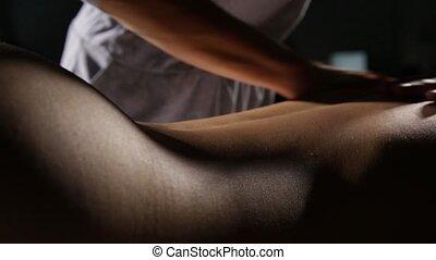 close-up back massage in spa salon. massage therapist does a...