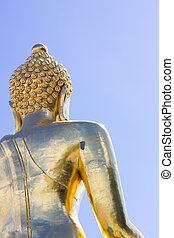 close-up back view big Buddha statue in thailand on blue sky bac