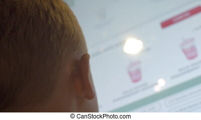 Close up back view of small blond boy choosing meals in fast food restaurant on touch screen