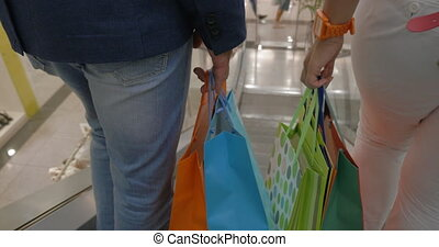 Close up back view of woman and man hands with paper bag