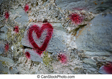 Close up background graffiti silhouette of red heart on an old relief stone wall