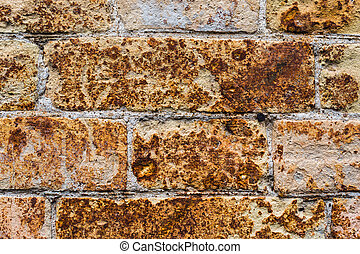 Close-up Background wall from an ancient yellow vintage brick with rusty corrosion patterns on the surface. Textured background in grunge style. Procurement for stylish graffiti