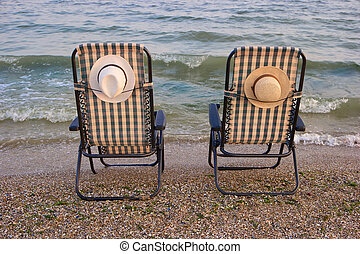 Close up backside view lounge chairs at a coastline.