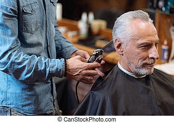 Close up barber trimming hair of old man