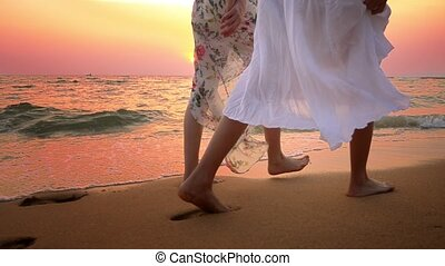 close up . bare feet on the beach. two young women in white...