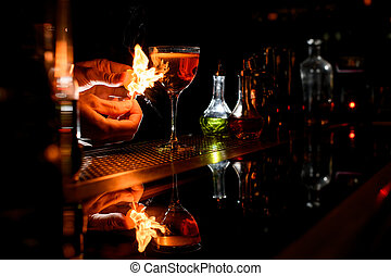 close-up bartender's hands which sets fire near cocktail glass.