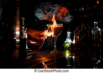 close-up bartender's hands which sets fire near cocktail wineglass.