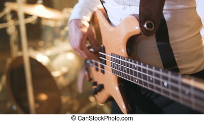 Guitarist wears white shirt playing on bass guitar on the concert stage, 100FPS slowmotion