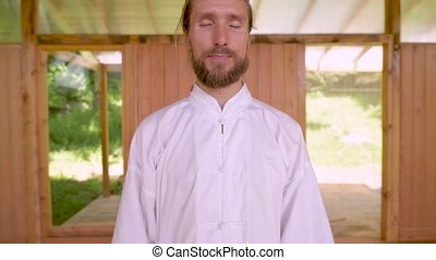 Close-up Bearded caucasian man wearing white clothes to practice concentration and breathing before practicing qigong tai chi.