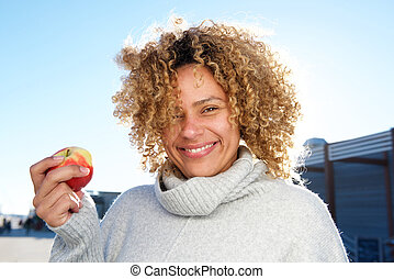 Close up beautiful african american woman holding apple
