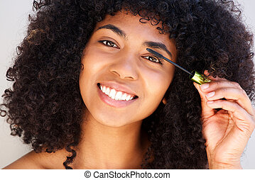 Close up beautiful african american woman putting on make up