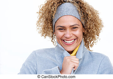Close up beautiful african american woman smiling with winter coat and headband by white background