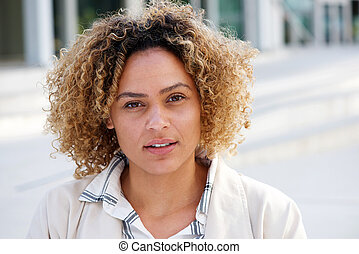 Close up beautiful african american woman with curly hair and staring