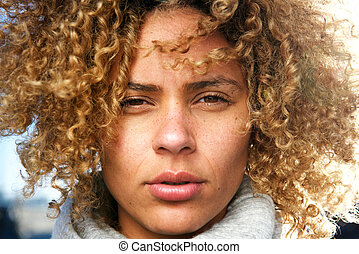Close up beautiful african american woman with curly hair staring