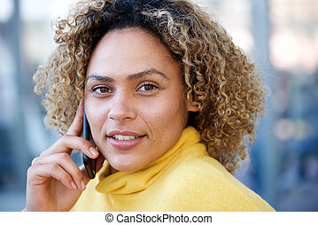 Close up beautiful african american woman with curly hair talking on mobile phone