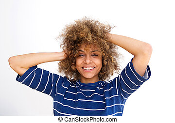 Close up beautiful african american young woman smiling with hands in hair against white wall