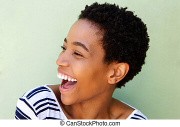 Close up beautiful african woman laughing against green background