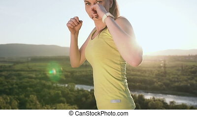 Close up. Beautiful kick boxing girl training on the top of mountain on sunset or sunrise at summer. Angry young woman doing boxing and looking on the camera. Beautiful female boxer training on the ourdoors in the morning