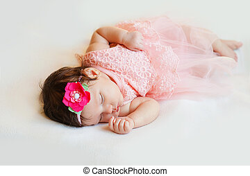 Close-up beautiful sleeping baby girl. Newborn , asleep on a blanket. portrait of , two month old, wearing large, fabric rose headband. Closeup photo