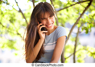 Close up beautiful smiling young woman talking with cellphone in park