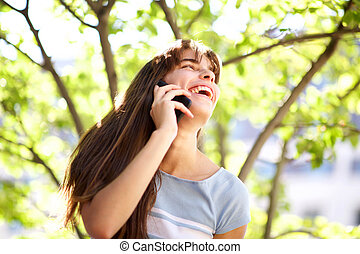 Close up beautiful smiling young woman talking with mobile phone in park