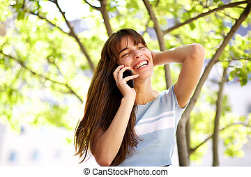 Close up beautiful smiling young woman talking with phone in park
