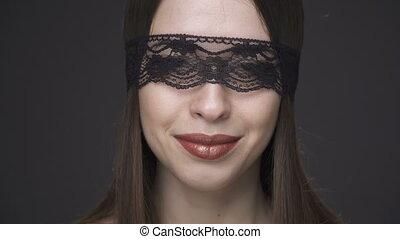 Close up beautiful woman's face in erotic lace headband...