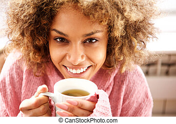Close up beautiful young african american woman drinking cup of tea