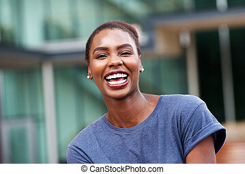 Close up beautiful young african american woman laughing outdoors
