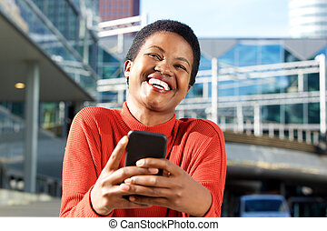 Close up beautiful young african american woman laughing with cellphone in city