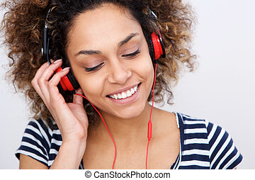 Close up beautiful young african american woman listening to music with headphones